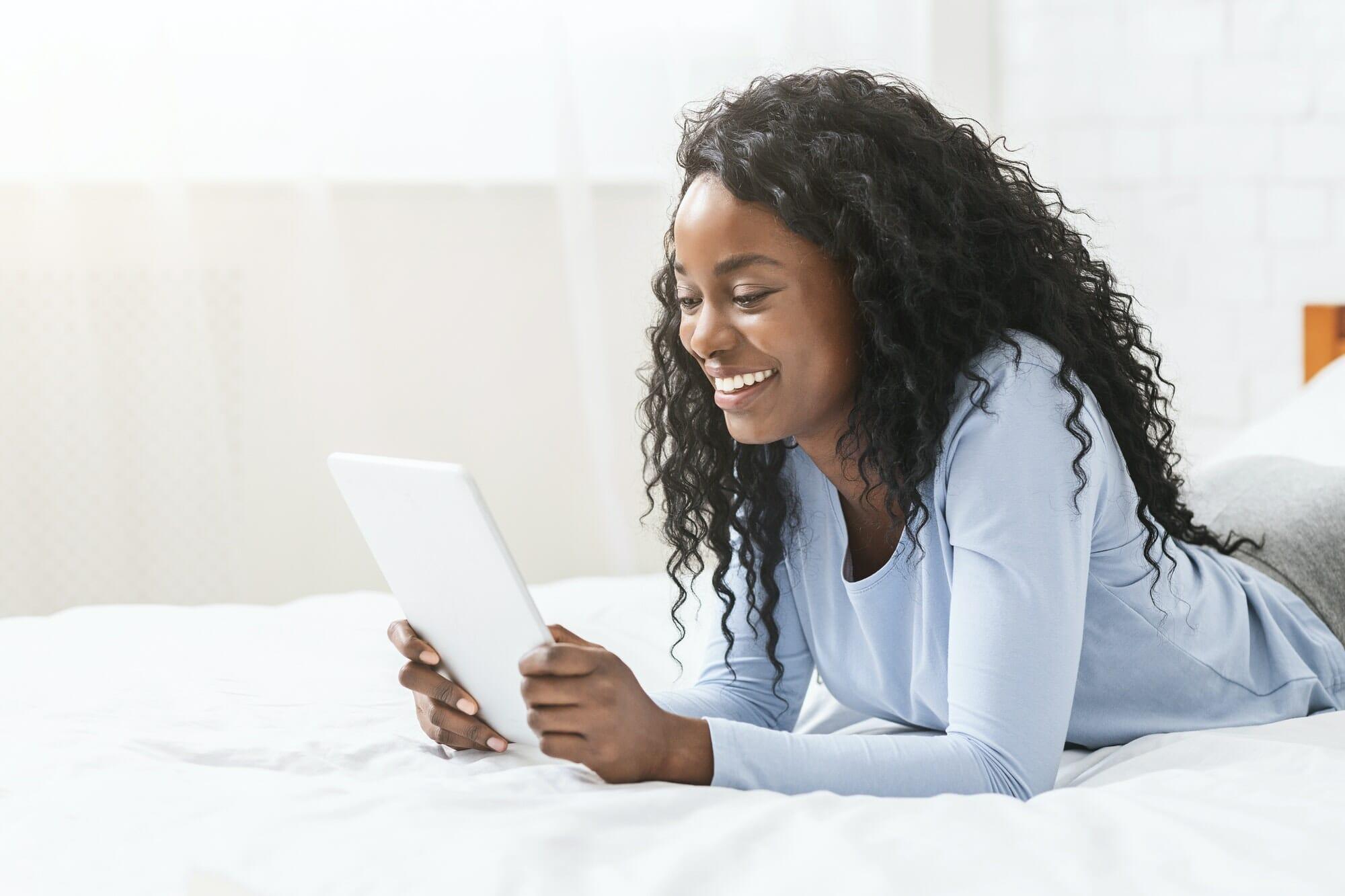 Girl reading blog on digital tablet in bed